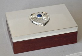 Wooden  box (rose wood)  decorated with silver or gold plated bronze and sterling silver microsculpture on the lid depicting a symbol or a logo